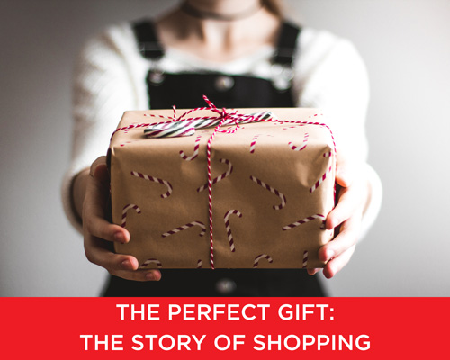 Person holding out holiday gift box with text 'the perfect gift: the story of shopping' on top